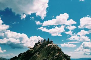 group-of-people-on-top-of-small-island-with-blue-sky-and-white-clouds